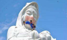 عمال يضعون قناعا على وجه تمثال ضخم بارتفاع 57 مترا- (شاهد)